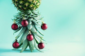 Creative Christmas tree made of pineapple and red bauble on blue background, copy space. Greeting card, decoration for new year party. Holiday concept.