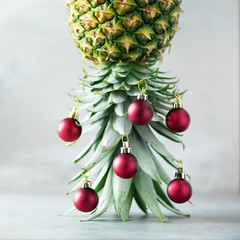 Creative Christmas tree made of pineapple and red bauble on grey concrete background, copy space. Greeting card, decoration for new year party. Holiday concept. Square crop