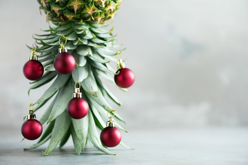 Creative Christmas tree made of pineapple and red bauble on grey concrete background, copy space. Greeting card, decoration for new year party. Holiday concept.