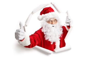 Santa Claus making thumbs up through a paper hole