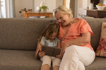 Grandmother and granddaughter using digital tablet in living
