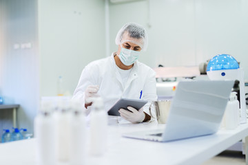 Picture of lotion bottles on production line. Bottles of cosmetic products in factory production line. Blurred picture of man using control panel in background.