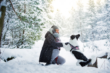 Woman playing with dog in snowy forest. Running and jumping happy pet, girl laughing, having fun. Beautiful winter landscape with trees in snow.