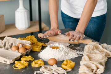 Close view of woman rolling dough for fettuccine pasta on black table