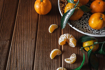 Fresh delicious mandarin oranges fruit or tangerines with green leaves in a bowl on wooden background