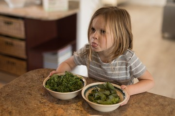 Girl holding bowl of green vegetables in kitchen