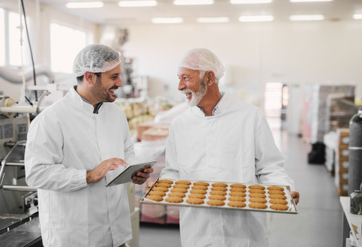 Picture of two employees in sterile clothes in food factory smiling and talking. Mature man is holding tray full of fresh cookies while the younger is holding tablet and checking production line.