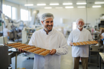 Picture of two happy smiling male employees in sterile clothes carrying trays full with fresh cookies in food factory. Helping each other and looking cheerful.
