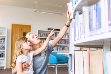 Mother with daughter choosing book in library