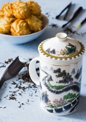 A teacup with 'Great wall' design, biscuits, tea, on delicate background