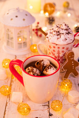 Cup with hot chocolate and marshmallows on old wooden table.