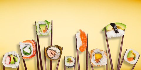 Traditional japanese sushi pieces placed between chopsticks, separated on pastel background.
