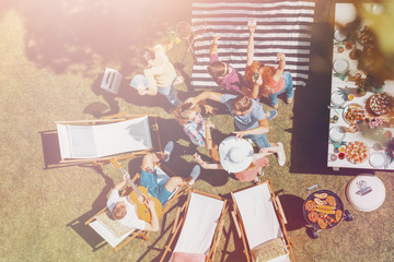 High angle on happy people dancing next to sunbeds and table with food in the garden