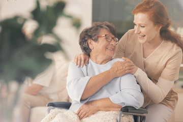 Smiling nurse supporting happy disabled elderly woman in the wheelchair