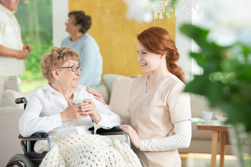 Happy nurse talking with smiling paralysed elderly woman in the wheelchair