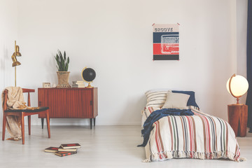 Poster above striped bed in white vintage bedroom interior with chair next to wooden cabinet. Real photo