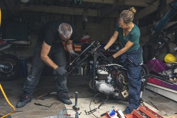 Mechanic repairing motorbike in garage
