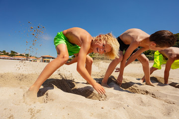 Cute boy digging holes with friends on sandy beach
