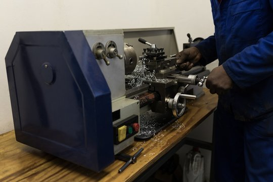 Blacksmith using machine in workshop