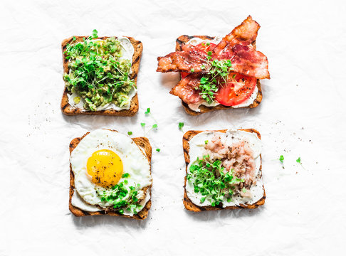 Choice of sandwiches for breakfast, snack, appetizers - avocado puree, fried egg, tomatoes, bacon, cream cheese, smoked mackerel grilled whole grain bread sandwiches. On a light background, top view
