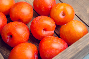 Fresh ripe plums on the rustic background. Selective focus. Shallow depth of field.