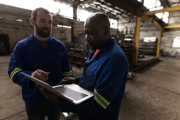 Two blacksmith discussing over laptop