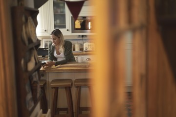 Pregnant woman texting on the phone in kitchen