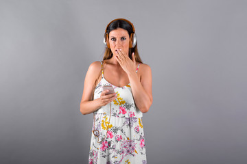 A beautiful surprised young woman listening to music and using her smartphone in front of a grey background in a studio.
