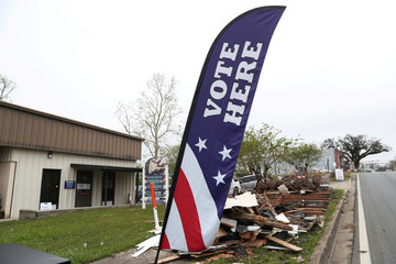 A voting sign is seen next to debris left over from Hurricane Michael in Marianna
