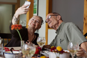 Senior couple taking selfie at Thanksgiving dinner table