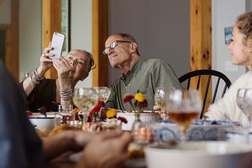 Grandparents taking selfie at Thanksgiving dinner table