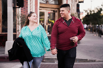 Smiling man and woman holding hands while crossing street in city