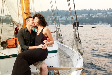 Smiling man and woman embracing while sitting on boat