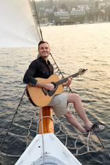 Smiling man playing guitar on a boat
