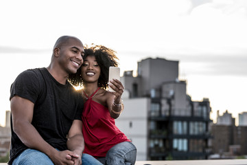 Smiling couple taking a selfie on a building terrace during sunset
