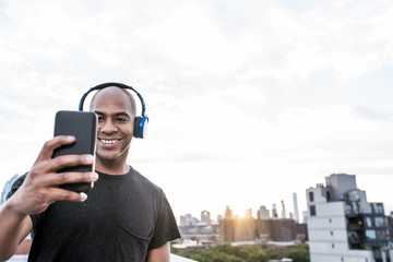 Man taking a selfie on a rooftop while wearing wireless headphones