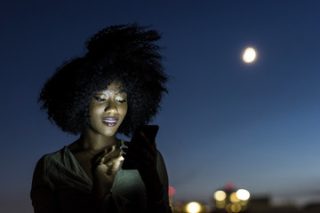 Woman using her cell phone with the moon in the background