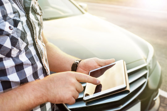 man with a tablet at the car on the road