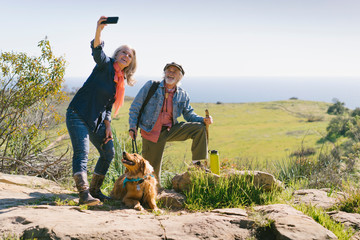 Man and woman taking a selfie with their dog