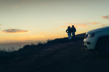 Rear view of couple looking at view while standing on hill during sunset