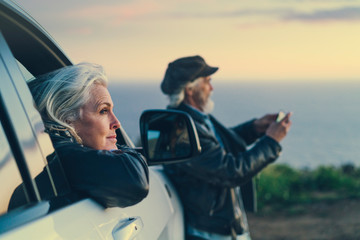 Woman leaning on car window while a man is taking a picture