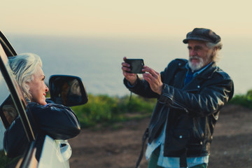 Man taking a picture of a woman leaning on a car window at countryside