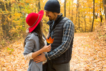 Smiling hikers looking at each other in forest during autumn