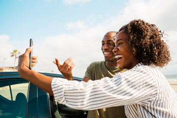 Couple taking selfie with a cell phone on by a car on a sunny day
