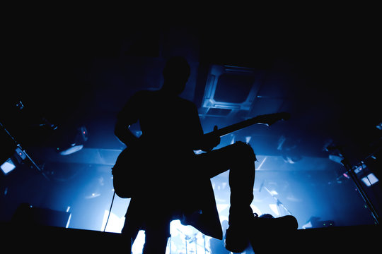Guitarist silhouette in darkness on a stage in blue back lights playing solo