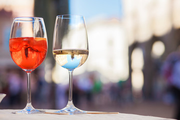 Chilled aperol spritz and prosesso glasses over Padova streets background