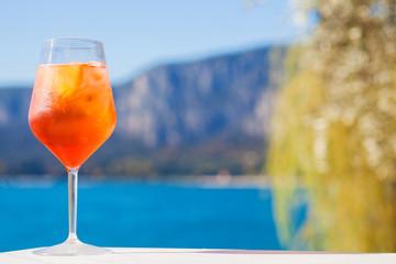 Glass of delicious Aperol Spritz cocktail on blurred sunny Lago di Garda background