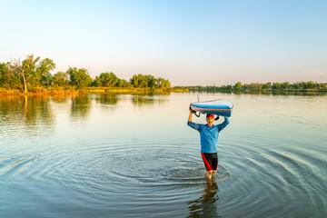 Launching stand up paddleboard on a lake