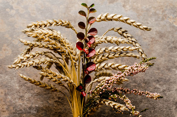 A bouquet of autumn flowers, wheat and heather collected on the field