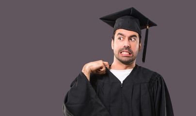 Man on his graduation day University with tired and sick expression on violet background
